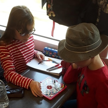 Picture of my son and daughter playing snakes and ladders on the train during our railadventure with Greater Anglia