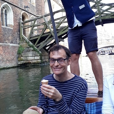 Picture of my husband eating an ice cream cone in a punt, with the punt chauffeur and mathematical bridge behind, during our family trip to Cambridge by train