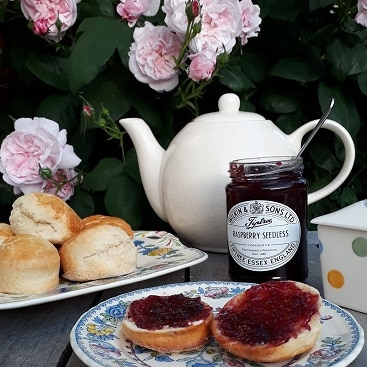 Picture of scones made from Sourced Locally shopping, on a table with Tiptrees jam, teapot and roses behind