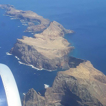 Picture from the aeroplane on the way to Madeira, with an island and bright blue sea