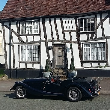 Photo of a classic car outside a half-timbered house for my house of what does being rich mean to you?