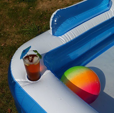 Picture of a paddling pool with beach ball and drink with umbrella for my post on how to entertain the kids for less in the summer holidays