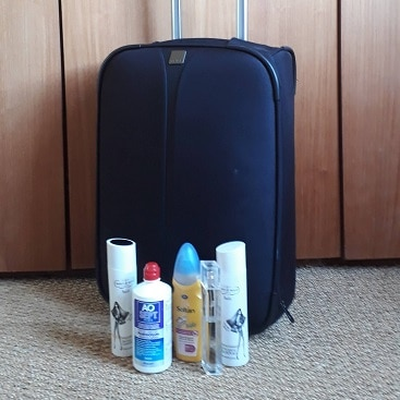 Picture of suitcase and bottles of toiletries for my post on how to cut the cost of taking liquids on flights