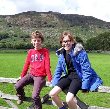 Picture of my two children sitting on a fence in the Lake District during our summer holiday