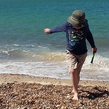 Picture of my son skipping along the pebbles at the seaside for my post on choosing a pension when you are self-employed