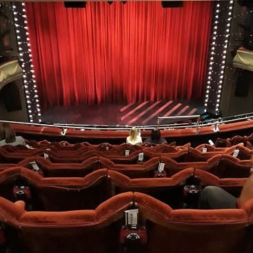 Picture of the theatre seats and curtain after buying cheaper tickets as one of our frugal things in London