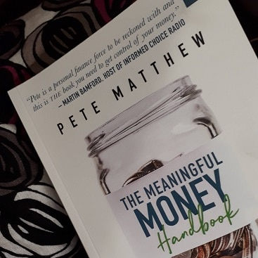 Picture of The Meaningful Money Handbook on my lap on the train
