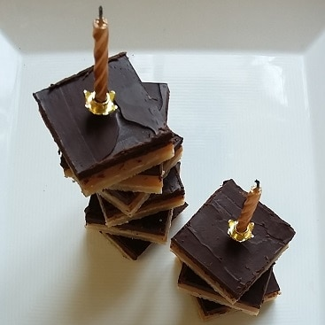 Picture of millionaire's shortbread stacked in towers with a couple of birthday cake candles