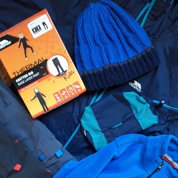 Picture of clothes for a school trip including waterproof jacket, trousers, thermal leggings, fleece and hat, bought in sales