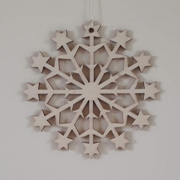 Picture of a wooden snowflake decoration on a cream background for a post with a plea for a little less Christmas
