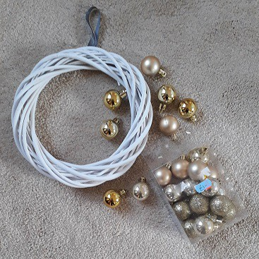 Picture of a box of baubles from a charity shop with my white rattan wreath