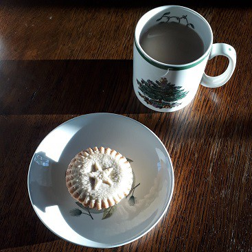 Picture of a mince pie on a plate with a Christmassy cup of tea