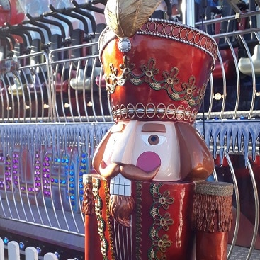 Picture of a giant Nutcracker statue by one of the rides at The North Pole
