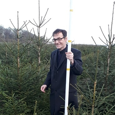 Picture of my husband holding the Christmas tree measuring stick for my five more festive frugal things post