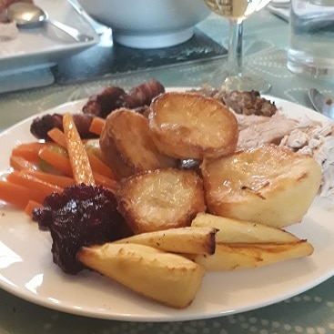 Picture of a plate of Christmas dinner with potatoes, parsnips,carrots and red cabbage