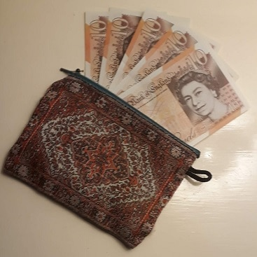 Picture of a purse with a sheaf of £10 pound notes for my post on financial resolutions