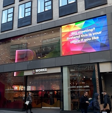 Picture of the outside of B Works in Manchester, with the sign 'Big meeting? Pretend this is your office if you like'