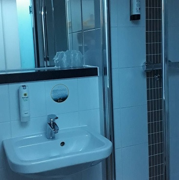 Picture of the sink, shower cubicle and refillable dispenses in the Point A Hotel Shoreditch bathroom
