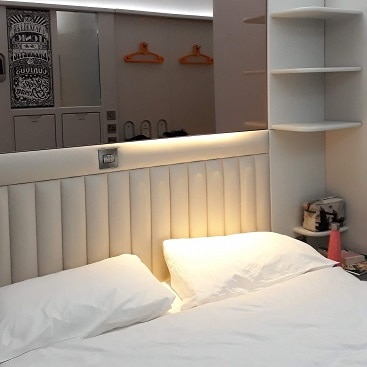 Picture of a hotel room at Point A Shoreditch showing white bed and shelves beside it