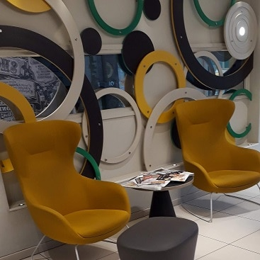 Picture of mustard colour chairs and round mirrors in the hotel lobby at Point A Shoreditch