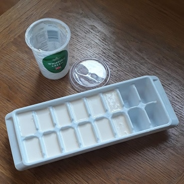 Picture of an empty pot of cream by an ice cube tray with cream in it