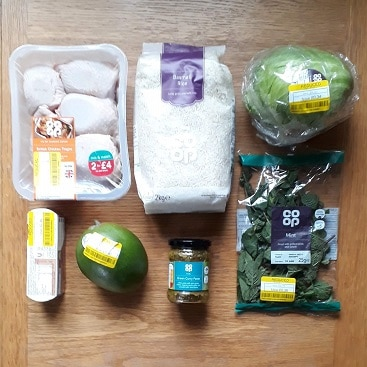 Picture of shopping with big bag of rice and yellow stickered food for my post with an update on cutting food costs in January