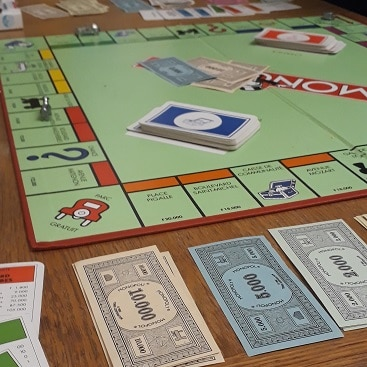 Picture of a monopoly board with paper money for my post with 9 quick money saving tips to do today