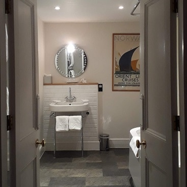 Picture of the bathroom with double doors, sink, circular mirror and framed picture for my post on The Ickworth Hotel for Valentine's Day