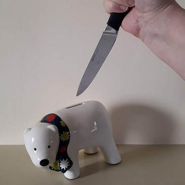 Picture of a knife stabbing towards a polar bear money box for my post about what parents need to know about student loans