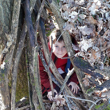 Picture of my son smiling inside the den he helped build during a frugal Febriary half term