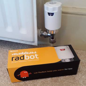 Picture of a Radbot smart radiator valve fitted on a radiator with the packaging