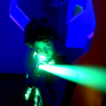 Picture of a child in in a jacket with light up panels shooting a beam of green laser from the Planet Laser in Bury St Edmunds website