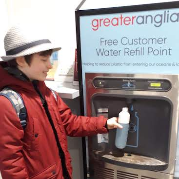 Picture of my son refilling his water bottle at the refill point in Ipswich station, before our trip to Bury St Edmunds