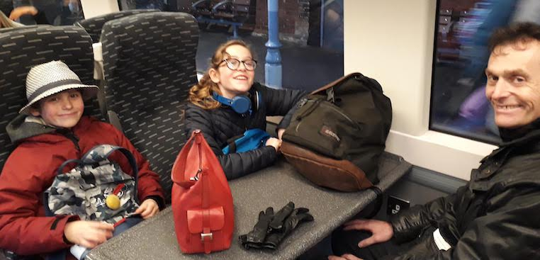 Picture of my husband and two children sitting round a table on the train from Bury St Edmunds to Ipswich