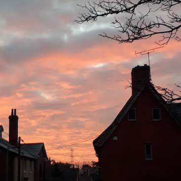 Picture of red skies above cottages for my post on what it feels like to be mortgage free