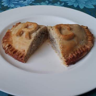 Picture of a pasty cut in half to show sardine and rice filling with R and C in pastry on top