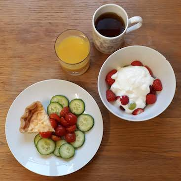 Picture of quiche and salad, orange juice, peppermint team, berries and yogurt