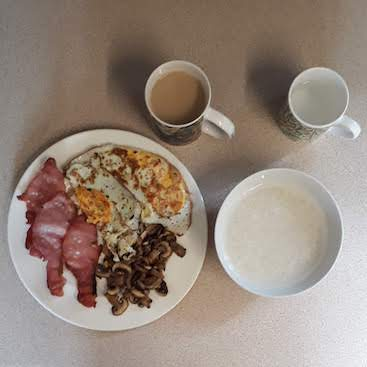 Picture of a fry up with bacon, egg and mushrooms and cup of tea on one side, and a mug of water and bowl of soaking rice starting the Ration Challenge on the other