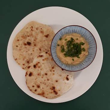 Picture of two flatbreads and some hoummous and spring onion, one of my meals on the Ration Challenge