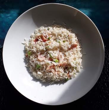 Picture of bacon fried rice with spring onion on.a white dish