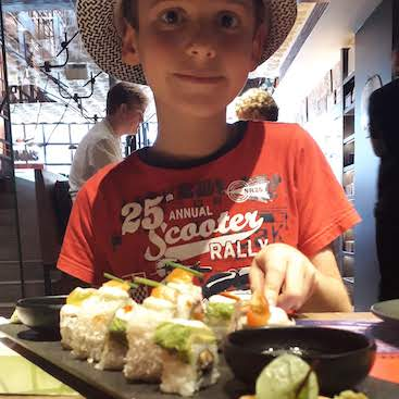 Picture of my son with a platter of sushi before our Kids Week theatre trip