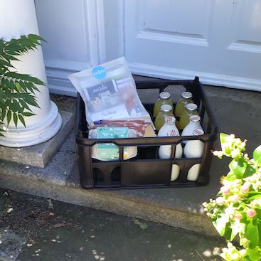 Picture of a crate with bottles, eggs, bacon and orange juice on my doorstep