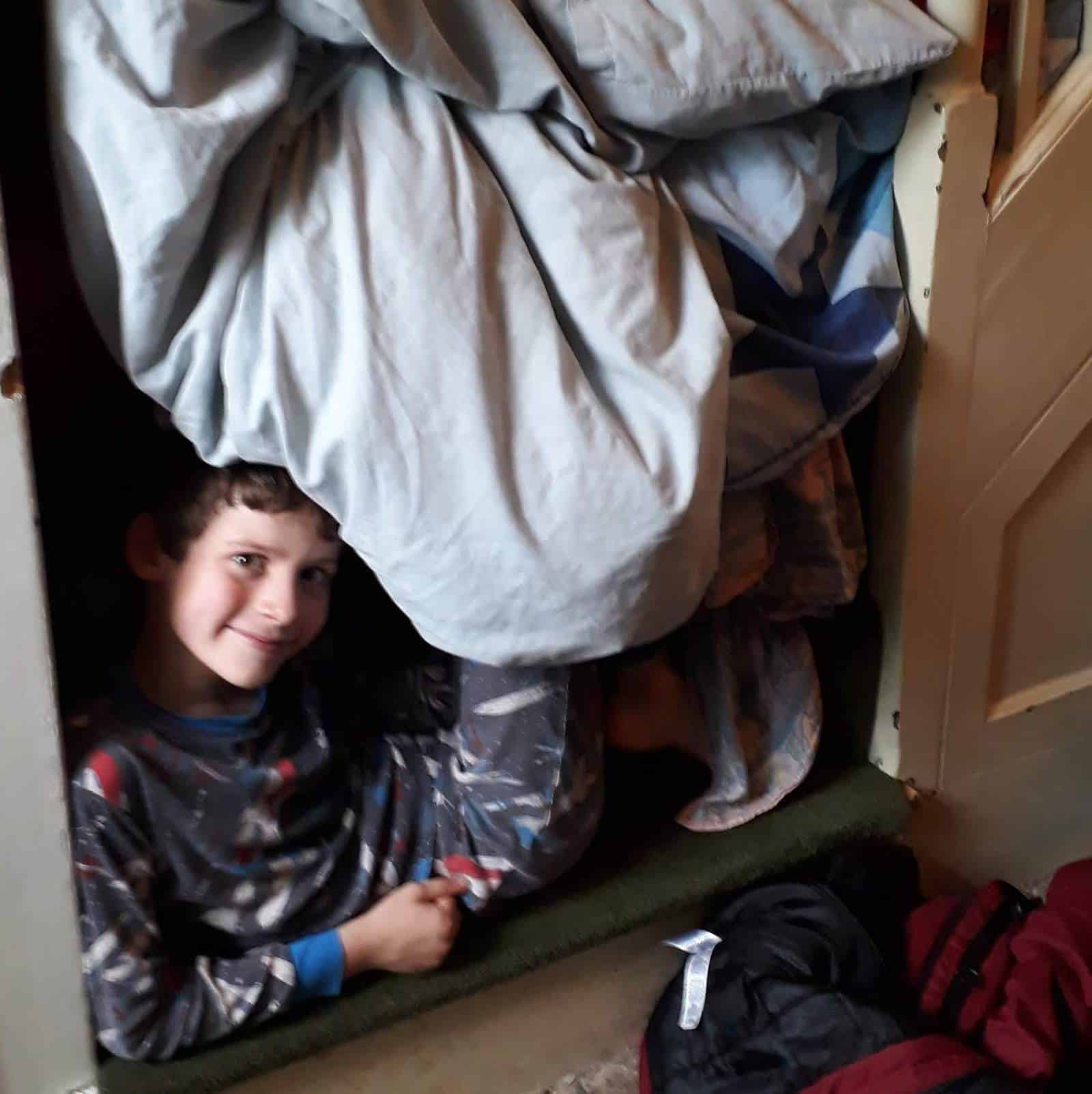 Picture of my son under a duvet den as one of my five frugal things for October