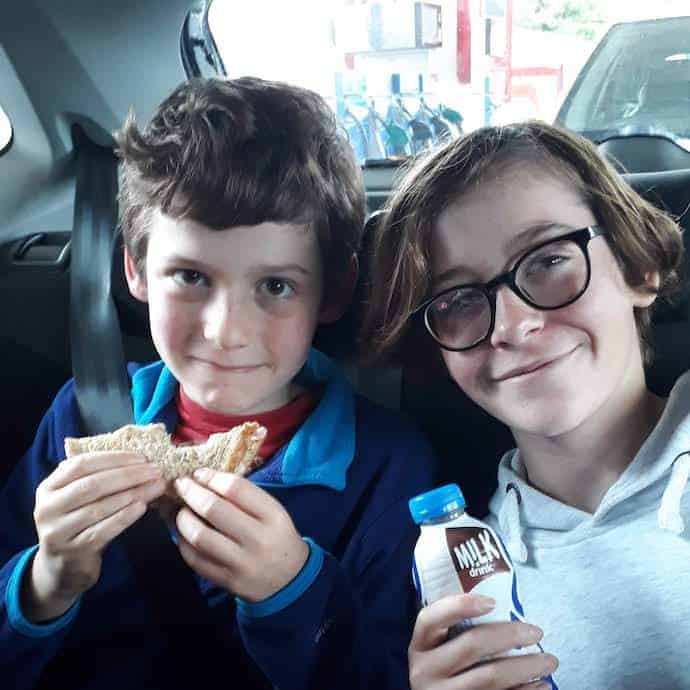 Picture of my two children clutching sandwiches and drinks from an Esso station
