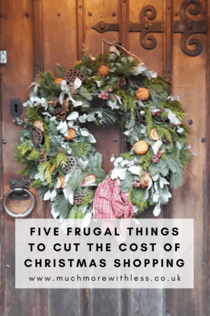 Pinterest size image of a Christmas wreath on a wooden for my post on how to cut the cost of Christmas shopping