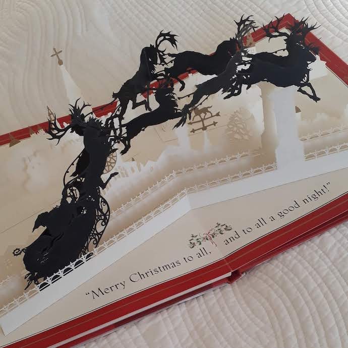 Pop up book with reindeer pulling Father Christmas on his sleigh