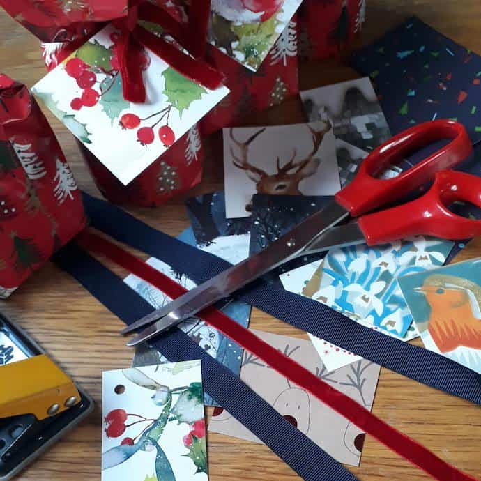 Picture of ribbons scissors and Christmas cards made into labels