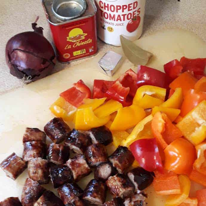 Picture of ingredients for sausage casserole, including chopped sausages and peppers