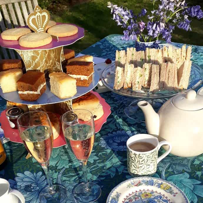 Picture of Tiptree cream tea on a cake stand with added sandwiches, teapot and glasses of fizz.