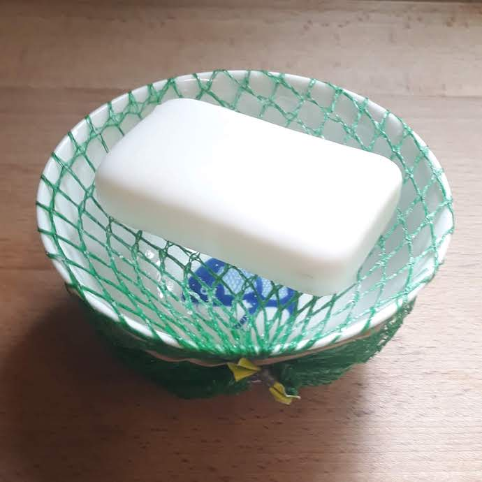 Picture of a bar of soap suspended on a plastic net bag above a bowl